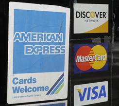 Credit card logos are posted at a store in Los Altos, Calif.