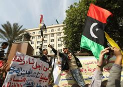 Protesters shout slogans against Libyan leader Moammar Gadhafi on Tuesday as they hold up the old Libya flag during a demonstration outside Arab League headquarters in Cairo.