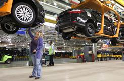 In the final assembly phase of production at Ford's Michigan Assembly Plant, in Wayne, Rashell Rule, 38, secures an under-body air deflector on Focus.