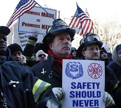 Elizabeth Fire Department firefighters Rick Maliniak, center left, and Andy Socha stand with other firefighters, police officers and their supporters in a large gathering in Trenton, N.J., during a rally to protest staff cuts and promote public safety.