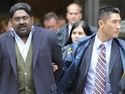 In this Oct. 16, 2009, file photo, Raj Rajaratnam, billionaire founder of the Galleon Group, a major hedge fund, is led in handcuffs from FBI headquarters in New York.
