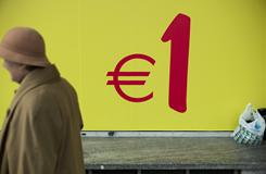 A woman walks past a sign on a supermarket window in Lisbon.