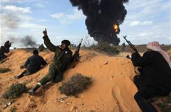 Libyan rebels take positions Wednesday while fighting government troops as a facility burns near the city of Ras Lanouf.