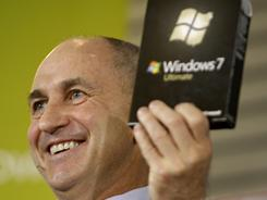 Chris Liddell, CFO of GM, holds up a copy of the Windows 7 computer operating system while he held the same job at Microsoft.