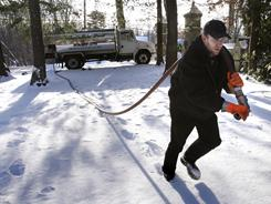 In this Jan. 5, 2010 file photo, Jason Kilpatrick of Wholesale Fuel hauls a hose across a snow covered yard while delivering home heating oil in Framingham, Mass.