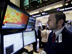Specialist Christopher Gildea watches images from the earthquake in Japan on a television screen at his post on the floor of the New York Stock Exchange on March 11, 2011.