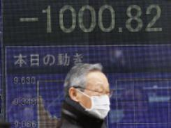 A man walks past a stock price board  March 15, 2011 in Tokyo.
