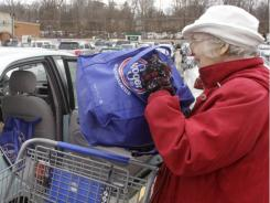 In this Feb. 1, 2011 photo, Lynne Curtiss places her reusable Kroger shopping bags in her car after shopping, in Cincinnati.