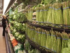 In this March 1, 2011 photo, a customer looks at fresh vegetables at a Kroger supermarket in Cincinnati.