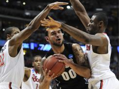 Gonzaga center Robert Sacre is double-teamed under the basket by St. John's Justin Brownlee, 32, and Dele Coke.