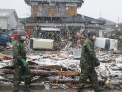 Japanese soldiers make their way across a sea of devastation in Natori, Miyagi prefecture on Wednesday.