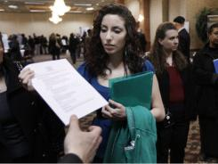 In this March 9, 2011 photo, job seeker Nicholle Marzouq hands a resume to a recruiter at a job fair in Southgate, Mich.