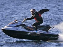 "Howard Garton, who refers to himself as ""OrcaMan,"" catches air as he speeds atop a personal watercraft Dec. 30 through Seattle's Elliott Bay."