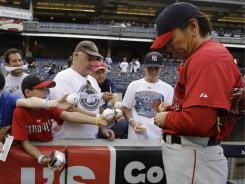 In this July 20, 2010 file photo, then, Los Angeles Angels' Hideki Matsui signs autographs for fans before a baseball game against the New York Yankees, Matsui's former team, at Yankee Stadium.