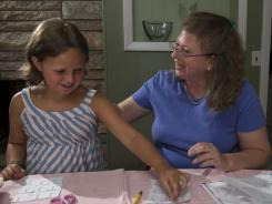 Brigitta Stone, right, helps her daughter Gillian with her math homework. Experts say it's a smart idea to help teach children about money and math.