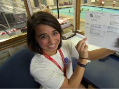 "Lifeguard Nicole Moro of Seattle holds up her paycheck in an episode of PBS' ""Biz Kid$."""