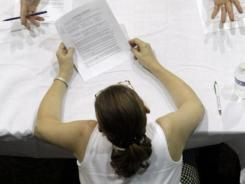 An applicant's resume is reviewed at a 2010 job fair in Southfield, Mich.