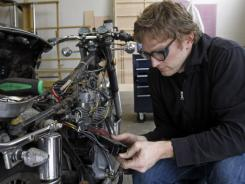 """Dream Coach"" Cody Culbertson works on his motorcycle at TechShop in San Francisco on  March 22, 2011."