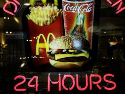 A neon sign reminds patrons at a McDonald's restaurant of the 24 hour service.