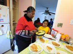 Josehine Wiles-Warner prepares plates of food for her family's breakfast as Abraham Kollie, 8, looks on.