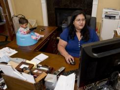 Swapna Patel of Katy, Texas, works from home with daughter Raina, 9 months, at her side.