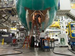 Elkan Reuben, bottom, and Brian Taylor work on the nose gear a 747-8 Intercontinental at a Boeing plant in Everett, Wash.