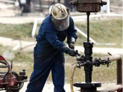 A worker repairs a well after it was shut down for maintenance at a Chevron oil field in Bakersfield, Calif.