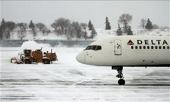 Crews work to clear the tarmac of snow Feb. 21 at Minneapolis-St. Paul International.