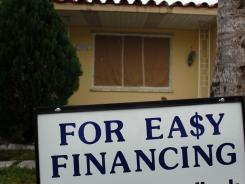 A sign advertising easy financing stands in front of a home for sale Feb. 11, 2011 in Miami.