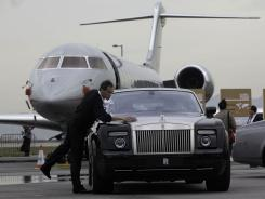 A man cleans a Rolls Royce limousine parked in front of a business jet in Hong Kong on March 9, 2011.   Personal use of the corporate jet has skyrocketed.