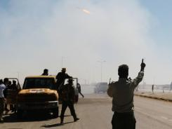 Rebel fighters celebrate as they fire powerful rockets toward Libyan Army positions on the outskirts of Ajdabiyah, Libya.