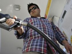 Daniel Dona pumps gas at a Shell station in Menlo Park, Calif.