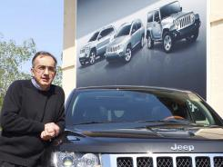 Fiat and Chrysler CEO Sergio Marchionne poses with the new Grand Cherokee Jeep during a presentation in Balocco, near Turin, Italy, April 11, 2011.