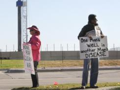 Protestors holds signs  accross the street from a working natural gas well in Flower Mound, Texas in November.