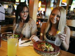 Kaila Mullins, right,  and her mother, Michelle Mullins, enjoy the meals they ordered from the under-550-calorie menu at Applebee's in Hurricane, W.Va.