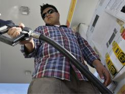 Daniel Dona pumps gas at a Shell gas station in Menlo Park, Calif.