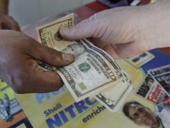 In this March 31, 2011 photo,  a customer pays cash for his gas at a Shell gas station in Menlo Park, Calif.