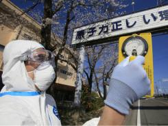 A man in radiation-proof suit checks radiation levels in an area not too far from the Fukushima nuclear power plant.