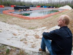In this file photo, hiker Bob Myers looks at part of a gas drilling operation in a state forest near Lock Haven, Pa.