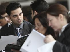 In this April 8, 2011 photo, job seekers wait in line to enter the 23rd annual CUNY Big Apple Job Fair in New York.