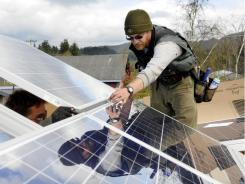 Seth Lucas and Sam Schwarz, left, install solar panels on the roof of the South Coast Food Share pantry in Myrtle Point, Ore.