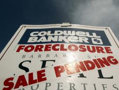 A foreclosed house sign with sale pending is shown in Tigard, Ore., on March, 8, 2011.