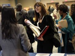 Job seekers talk to employers at a job fair in New York on April 18, 2011.