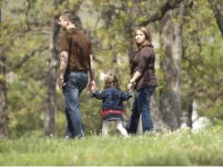 Laura Maxwell and her daughter Emma and husband Kyle walk through a park near their apartment in Fayetteville, Ark.
