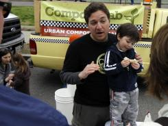 This April 10, 2011 photo shows Jeremy Brosowsky, with his son Gideon Brosowky, 3, as he talks about composting near his Compost Cab in Washington.