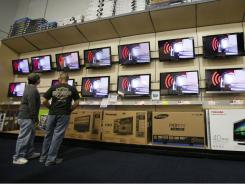 People shop for televisions at a Best Buy in Glendale, Calif., in April 2011.