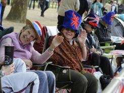 Sally Stoodley of Alton, Hampshire, left, and Julie Cavanagh, also of Alton, wave as they sit along The Mall April 28  to get a front row seat to Friday's Royal Wedding.