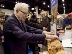 Berkshire Hathaway Chairman and CEO Warren Buffett picks up a box of Sees Candies, a Berkshire subsidiary, at the exhibit floor of the Qwest Center in Omaha, Neb., Saturday.