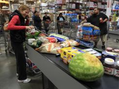 In this April 28, 2011 photo, Costco shoppers load the conveyer belt at the check-out counter at Costco in Mountain View, Calif.