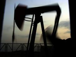 An oil pump works at sunset April 29, 2011 in the desert oil fields of Sakhir, Bahrain.